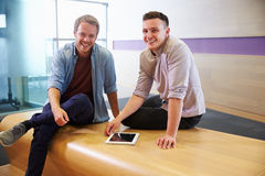 Two casually dressed men using a tablet, looking to camera Royalty Free Stock Photography