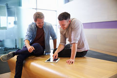 Two casually dressed young men using a digital tablet Royalty Free Stock Photos