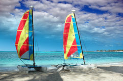 Two catamarans on a beach. Two colorful catamarans on a tropical beach Royalty Free Stock Images