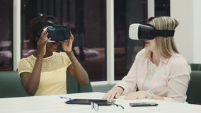 Two caucasian and afro-american women using virtual reality glasses stock footage