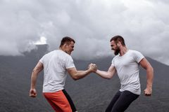 Two caucasian athletes in sportive wear measuring forces at outdoor training. Two caucasian athletes in sportive wear measuring forces at outdoor crossfit royalty free stock image