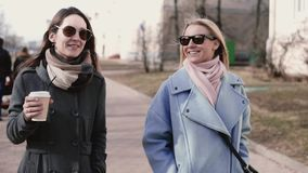 Two Caucasian attractive girls walk together. Slow motion. Adult female friends in stylish clothes sunglasses chatting. Two Caucasian attractive ladies walk stock footage