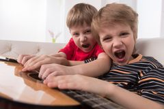 Two caucasian boys playing acoustic guitar. Royalty Free Stock Photography