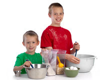 Two caucasian brothers baking a cake. Two beautiful caucasian brothers making a cake in the kitchen, smiling happily, isolated on white background Stock Images