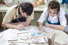 Two Caucasian Ceramists Painting and Glazing Clay Crafts Together. In Workshop with Paintbrushes.Horizontal Image Composition Stock Photos