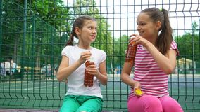 Two caucasian children telling secrets, laughing and drinking in park, outdoors. Leisure time park. Health, wellness, food concept stock video footage