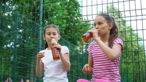 Two caucasian children telling secrets, laughing and drinking in park, outdoors. Leisure time park. Health, wellness, food concept stock footage