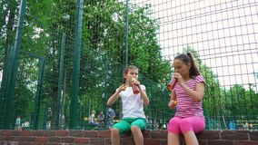 Two caucasian children telling secrets, laughing and drinking in park, outdoors. Leisure time park. Health, wellness, food concept stock video