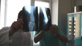 Two caucasian doctors view mri picture and discussing about it. Medical workers in hospital examine x-ray prints. Male stock video