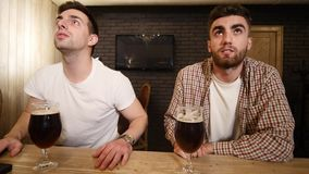 Two caucasian friends celebrating success of their sport team at the pub. Attractive young men hugging at the bar. Counter. Glad sport fans clinking their stock video