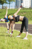 Two Caucasian Girlfriends Having Arms and Body Stretching Exercises Outdoors Stock Images