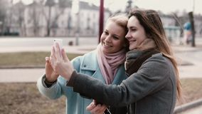 Two Caucasian girlfriends posing for a selfie. Adult 30s women spend time together and have fun posting funny pictures. Two Caucasian girlfriends posing for a stock video footage