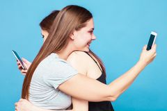 Two young women make the photo of eath other huging. Two caucasian girls with brown hair huging tape something on the back of each other. Blue background, studio royalty free stock image
