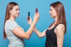 Two young women make the photo of eath other royalty free stock photos