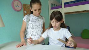 Two caucasian girls doing homework. Discussing lessons. pupils studying at home. one girl helping another stock footage