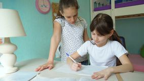 Two caucasian girls doing homework. Discussing lessons. pupils studying at home. one girl helping another stock video footage