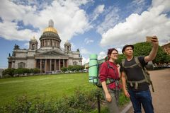 Two caucasian hikers taking selfies in front of historic cathedral. Telephoto shot Royalty Free Stock Photo