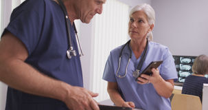 Two caucasian mature doctors or nurses on tech devices Royalty Free Stock Photos