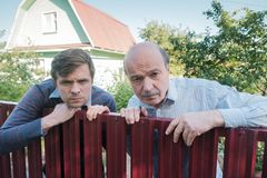 Two caucasian men carefully watching over the fence. Two angry caucasian men carefully watching over the fence. Concept of curious neighbors and private life royalty free stock photos