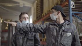 Two Caucasian men in face masks discussing work plan in warehouse. Portrait of professional male employees working at