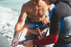 Two Caucasian men kitesurfers preparing equipment Stock Images