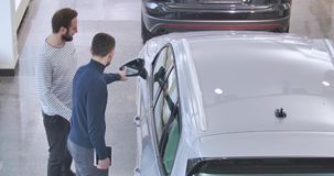 Two Caucasian men standing next to the silver jeep in car dealership and talking. Male trader with tablet and customer