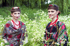 Two caucasian slavonic women sitting in the field of flowers Royalty Free Stock Images