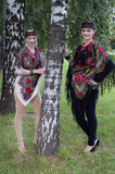 Two caucasian slavonic women standing near the birch tree. Two caucasian slavonic women in national costumes standing near the birch tree Stock Photo