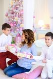 Two caucasian sons gifted present for mother near decorated fir tree. stock photography