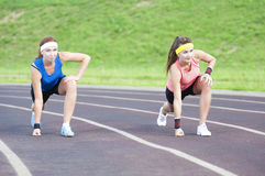 Two Caucasian Sportswomen in Professional Sportsgear Standing Prepared to Run On Sport Venue Outdoors Royalty Free Stock Images