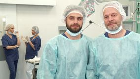 Two surgeons pose at the surgery room. Two caucasian surgeons of different ages posing at the surgery room. Bearded male doctors standing against background of Stock Photos