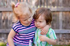 Two Caucasian Toddlers. Sitting together and hugging, outdoors, fence in background Stock Photo