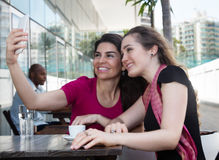 Two caucasian woman taking selfie with phone in a restaurant Royalty Free Stock Photo