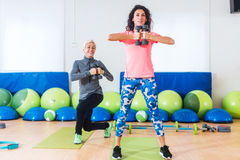 Two Caucasian women doing exercises with dumbbells working out indoors in aerobics class.  Royalty Free Stock Images