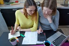 Two Caucasian women Housewives girlfriends sitting at the kitche. N table with a stack of papers, bills, notices from banks, a laptop and a calculator and count Royalty Free Stock Photography