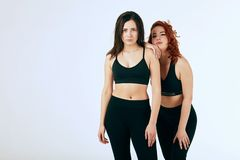 Two caucasian women standing together in black tank tops and leggings on white stock images