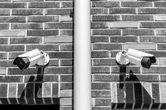 Two cctv surveillance security system cameras on the brick wall of luxury residential building for public and private safety black stock photography