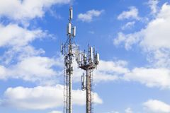 Two cell towers against the blue sky with clouds. Mobile communications and communications. royalty free stock photos