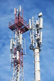 Two cellular base station tower. Two telecom cellular base station towers at blue sky with clouds royalty free stock image