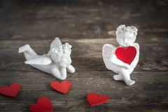 Angels with hearts icons of love and valentine`s day. Two ceramic angels. They have red hearts in their hands Royalty Free Stock Images