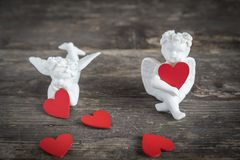 Angels with hearts icons of love and valentine`s day. Two ceramic angels. They have red hearts in their hands Stock Photo