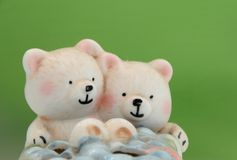 Two ceramic bears. Isolated on green background royalty free stock photo