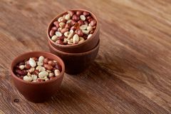 Two ceramic bowls with raw peanuts mix isolated over rustic wooden backround, top view, close-up. Two ceramic bowls shelled raw peanuts mix isolated over rustic Stock Images
