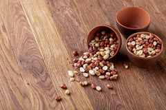 Two ceramic bowls with raw peanuts mix isolated over rustic wooden backround, top view, close-up. Two ceramic bowls shelled raw peanuts mix isolated over rustic Royalty Free Stock Image