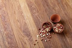 Two ceramic bowls with raw peanuts mix isolated over rustic wooden backround, top view, close-up. Two ceramic bowls shelled raw peanuts mix isolated over rustic royalty free stock photos