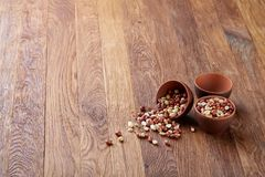 Two ceramic bowls with raw peanuts mix isolated over rustic wooden backround, top view, close-up. Two ceramic bowls shelled raw peanuts mix isolated over rustic stock photos