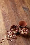 Two ceramic bowls with raw peanuts mix isolated over rustic wooden backround, top view, close-up. Two ceramic bowls shelled raw peanuts mix isolated over rustic stock photography