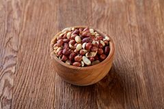 Two ceramic bowls with raw peanuts mix isolated over rustic wooden backround, top view, close-up. Two ceramic bowls shelled raw peanuts mix isolated over rustic royalty free stock photo