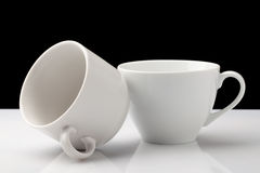 Two ceramic cups. On a white table, on a black background Stock Image