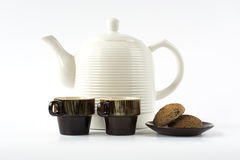 Two ceramic cups with cookies on a dish and a ceramic kettle on Royalty Free Stock Photo